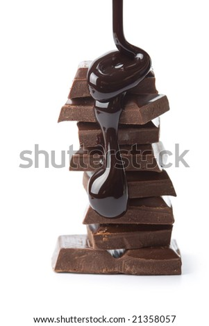 chocolate syrup being poured onto chocolate pieces isolated - stock photo
