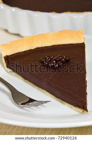 Chocolate tart dessert in a white plate. Very shallow depth of field. - stock photo