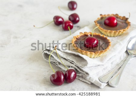 Chocolate tart with cherry. Homemade mini cherry tart with chocolate ganache on gray background. Place for text, copy space - stock photo