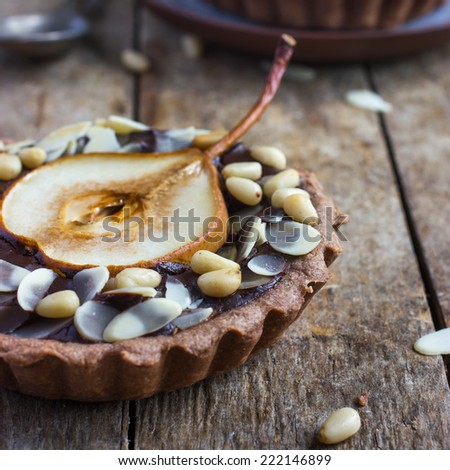 chocolate tartlets with pear and nuts on a wooden background, selective focus, square image - stock photo
