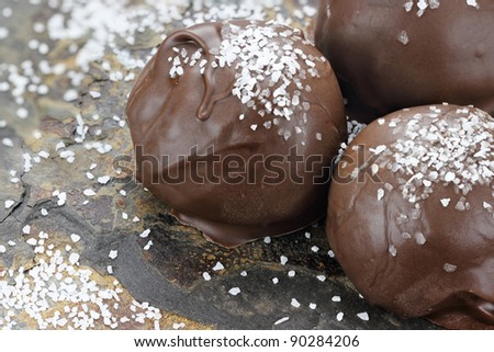 Chocolate truffle candies with sea salt. Shallow depth of field with selective focus on first truffle. - stock photo