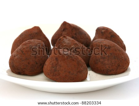 Chocolate truffle pralines sweets covered in cocoa powder on white plate and backgroun - stock photo