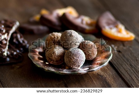 Chocolate, truffles and orange slices in dark chocolate on a wooden table - stock photo