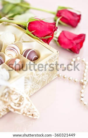 Chocolate truffles and red roses with copy space