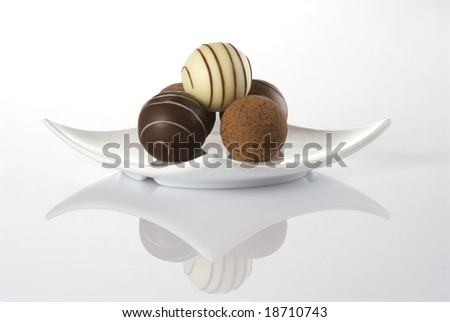 Chocolate truffles in a white plate isolated over a white background - stock photo
