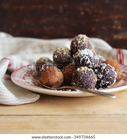 Chocolate truffles with chopped nuts, shredded coconut and cocoa powder on a dessert plate on a wooden rustic table, selective focus - stock photo