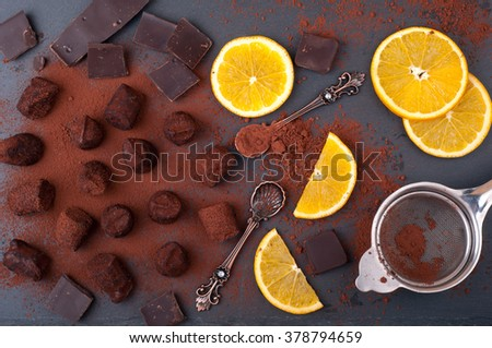 Chocolate truffles with orange and cinnamon. Candy, chocolate, citrus, vintage dessert spoons on stone background. Process of cooking of homemade sweets. Top view - stock photo