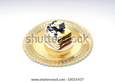 Chocolate, vanilla and cream cookie on a golden plate - stock photo