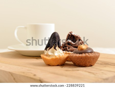 chocolate, vanilla and hazelnut  pastry with a White coffee cup on a wooden board shallow dof - stock photo