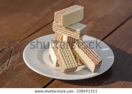 Chocolate wafer biscuits on saucer on a wooden table