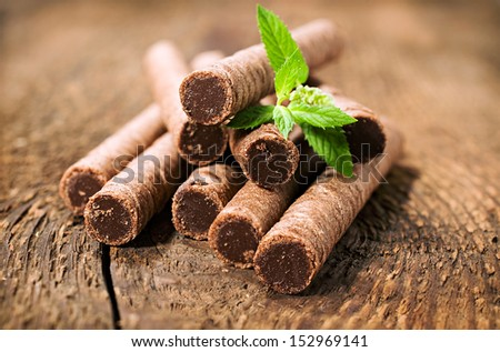 chocolate wafer rolls with leaves of mint on wooden background - stock photo