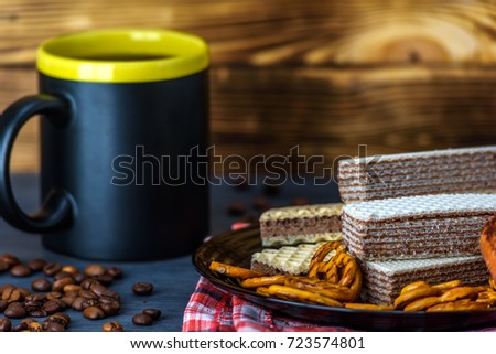 chocolate wafers and coffee on a dark background