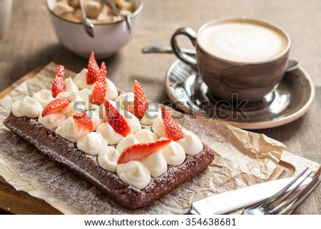 Chocolate waffle with whipped cream and strawberries on wooden table