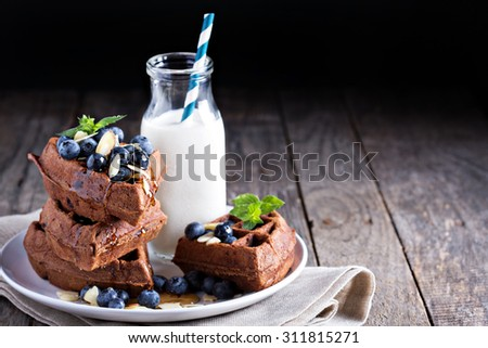 Chocolate waffles with milk and berries for breakfast - stock photo