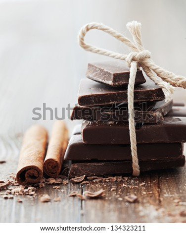 Chocolate with cinnamon sticks on vintage wooden background, selective focus - stock photo
