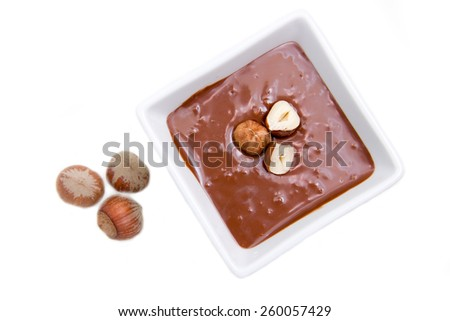 Chocolate with hazelnuts on a white background top view - stock photo