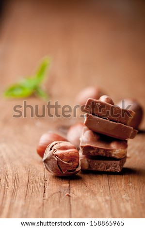 chocolate with hazelnuts on wooden planks - stock photo