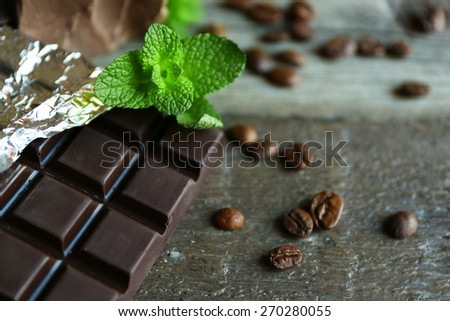 Chocolate with mint and coffee beans on wooden background - stock photo