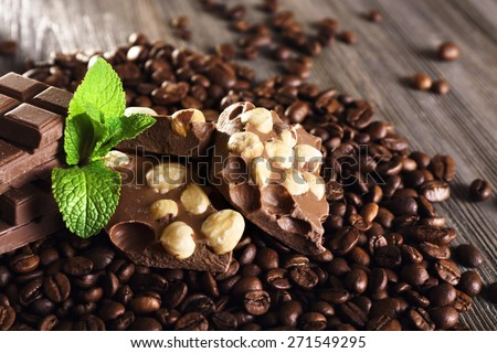Chocolate with mint and coffee beans on wooden table, closeup - stock photo