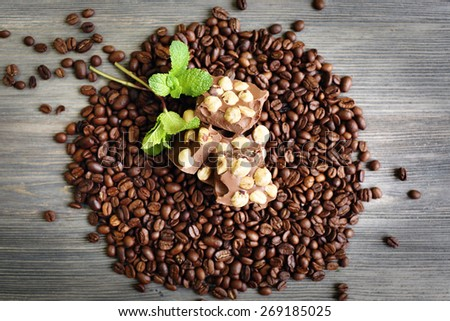 Chocolate with mint and coffee beans on wooden table, top view - stock photo