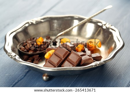 Chocolate with orange peels and coffee beans in metal tray on wooden background - stock photo