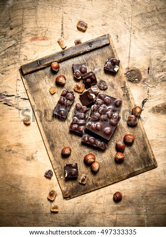 Chocolate with whole nuts. On wooden background.