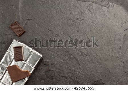 Chocolate wrapped in aluminum foil on dark slate. Advertising on chocolate. Sales chocolate . Packing chocolate. Chocolate shop. Sweet chocolate bar. - stock photo