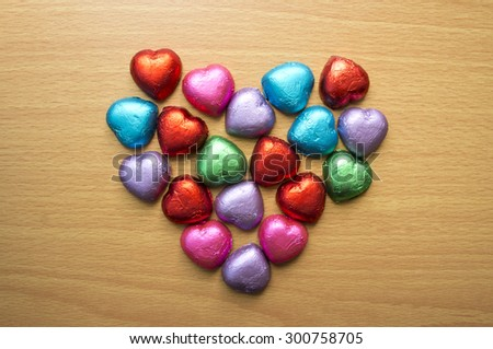 Chocolate wrapped in foil arranged in a heart shape. - stock photo