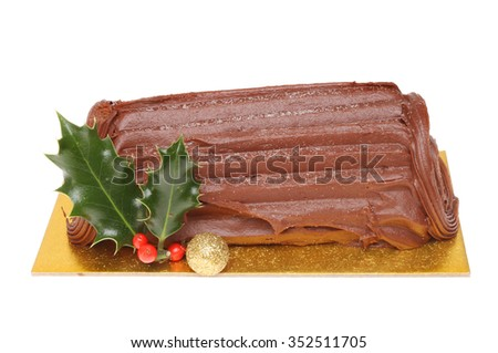 Chocolate Yule log decorated with holly and a Christmas bauble isolated against white - stock photo