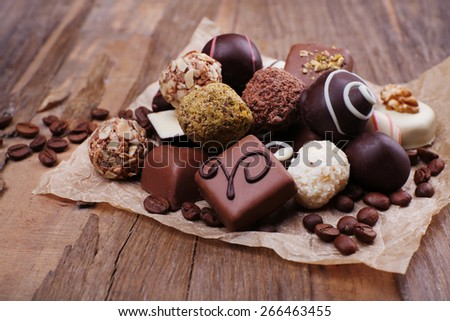 Chocolates assorted on crumble paper with coffee beans on wooden rustic background - stock photo