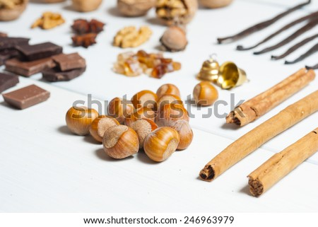 chocolates, hazelnuts, cinnamon rolls in a row on white wooden table background - stock photo