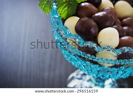chocolates in a glass bowl on a black wooden background. festivals and events. selective focus.close-up - stock photo