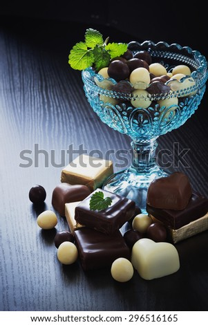 chocolates in a glass bowl on a black wooden background. festivals and events. selective focus - stock photo
