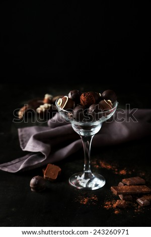 Chocolates in glass on black background - stock photo