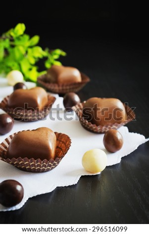 chocolates in the shape of hearts on a black wooden background. holidays & events. selective focus - stock photo