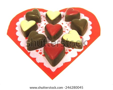 Chocolates on an lace paper and a red heart over white - stock photo