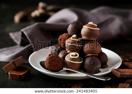 Chocolates on plate on black background - stock photo