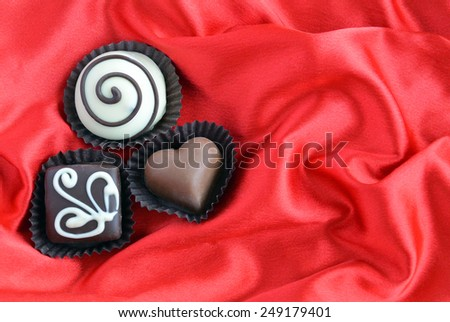 chocolates on red background - stock photo
