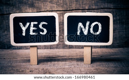 Choice between yes or no. Chalk writings on blackboards, choice between yes or no, on wooden background - stock photo