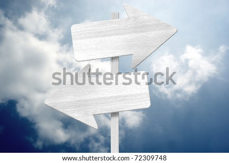 choice direction sign on the cloudy sky - stock photo