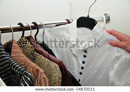 choice of a white blouse from a wardrobe - stock photo