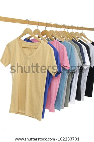 Choice of man clothes of different colors t-shirt on wooden hangers