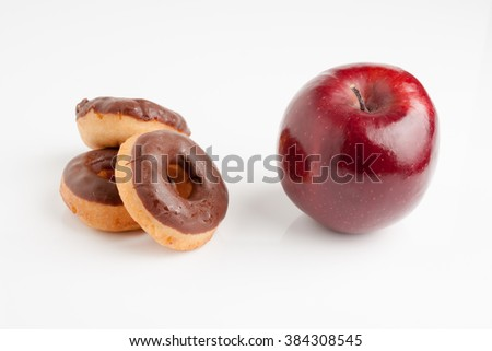 Choices choices! Chocolate donuts or a nice healthy shiny red apple a diet or junk food concept - stock photo