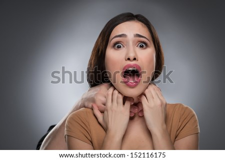 Choking. Portrait of shocked young woman with someones hands choking her while isolated on grey