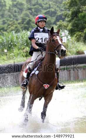 CHONBURI, THAILAND - JULY 27:Ho Yuen Yan Annie of Hongkong with Super Combed in action during 1st FEI Asian Eventing Championships 2013 at Thai Polo&Equestrian Club on July 27, 2013 in Chonburi, Thailand. - stock photo