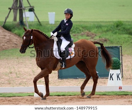 CHONBURI, THAILAND - JULY 26:Naphatra Lerdsilpjaroen of Thailand with Adventurer in action during 1st FEI Asian Eventing Championships 2013 at Thai Polo&Equestrian Club on July 26, 2013 in Chonburi, Thailand. - stock photo