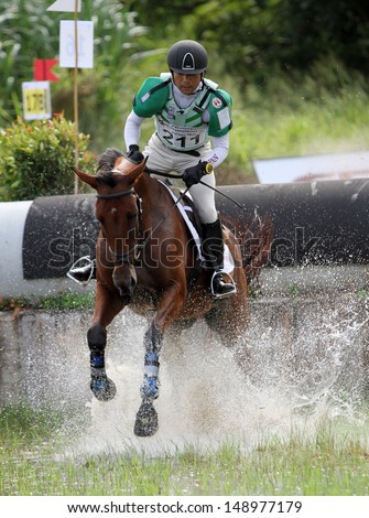 CHONBURI, THAILAND - JULY 27:Negishi Atsushi of Japan with Rata 21 in action during 1st FEI Asian Eventing Championships 2013 at Thai Polo&Equestrian Club on July 27, 2013 in Chonburi, Thailand. - stock photo