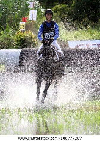 CHONBURI, THAILAND - JULY 27:Supanut Wannakol of Thailand with O-RE-O in action during 1st FEI Asian Eventing Championships 2013 at Thai Polo&Equestrian Club on July 27, 2013 in Chonburi, Thailand. - stock photo