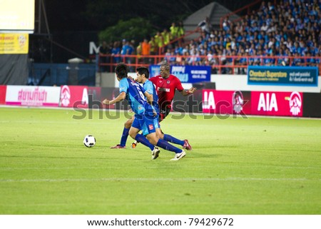 CHONBURI THAILAND- JUN 4 : K.CHRISTIAN (R) in action during Thai Premier League (TPL) between Chonburi Fc (Blue) vs Muang Thong utd (Red) on Jun 4, 2011 at Chonburi Stadium,Chonburi, Thailand - stock photo