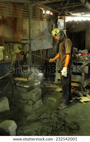 Chonburi, Thailand - Nov 17, 2014 - an unidentified man works on making stone mortar with homemade machine